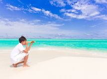 Boy with telescope on beach. Young boy looking through telescope on tropical, beach with blue sky and cloudscape background stock image