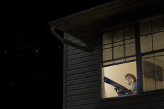 Boy With Telescope Looking At Night Sky. Young boy with telescope at open window looking at night sky Royalty Free Stock Images