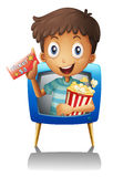 A boy on the television holding a ticket and a popcorn Royalty Free Stock Image