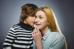 Boy telling his mother a family secret - isolated over gray background.  Royalty Free Stock Photography