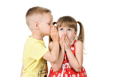 Boy is telling a secret to a girls ear. Boy whispers a secret in the ear of the girl Stock Photography