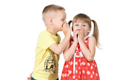 Boy is telling a secret to a girls ear. Boy whispers a secret in the ear of the girl Royalty Free Stock Photo