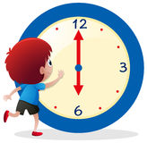 Boy telling time on blue clock Royalty Free Stock Image