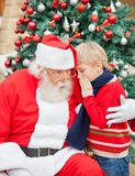 Boy Telling Wish In Santa Claus's Ear Royalty Free Stock Image
