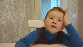 Boy tells a story at the table stock video footage