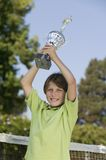 Boy on tennis court Holding up Tennis Trophy portrait Royalty Free Stock Photography