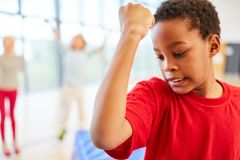 Boy tenses his biceps. African boy is exercising his biceps in elementary school physical education stock photos