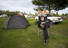 Boy and tent. A boy sitting next to a tent, reading a book. Camp site, Norway Royalty Free Stock Images