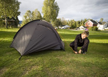 Boy and tent. A boy putting up a green, igloo type tent royalty free stock image