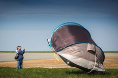 A boy with a tent in the field. Very strong wind, the tent flies away. Flying tent Summer, windy. A boy with a tent in the field. Very strong wind, the tent stock images