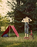 Boy with tent in meadow. Boy with orange tent, binoculars and oil lamp in meadow Royalty Free Stock Photo