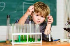 Boy test tubes colorful liquids chemistry school classroom. Kid study chemistry. Biotechnology and pharmacy. Genius stock photo