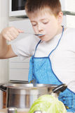 Boy testing soup from pan Royalty Free Stock Images