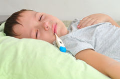 Boy with a thermometer in his mouth lying in bed Stock Images