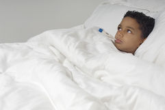 Boy With Thermometer Lying In Bed Royalty Free Stock Images