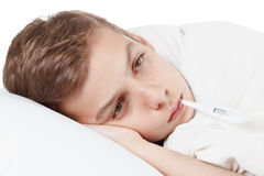 Boy with the thermometer preparing for treatment procedures. Boy with the flu and thermometer preparing for treatment procedures Stock Photo