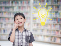 Boy think with light bumb in library Royalty Free Stock Photography