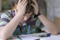 Boy thinking. A boy hardly solving homework Stock Photos