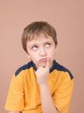 Boy thinking. Young boy thinking hard isolated on beige Stock Photo