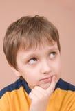 Boy thinking. Young boy thinking hard isolated on beige Stock Image