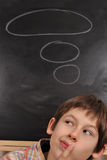 Boy is thinking. The boy is thinking by the blackboard Stock Photo
