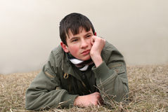 Boy thinking. Young boy lying on brown grass thinking Royalty Free Stock Photography