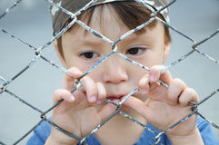 Boy thinking behind bars Stock Photography