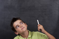 Boy thinking on the board. Portrait of boy in school thinking on the Board Stock Photography