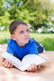 Boy thinking on the book. Boy lying on picnic and thinking on the book. Selective focus royalty free stock photography