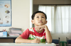 The boy thinking in classroom Stock Image