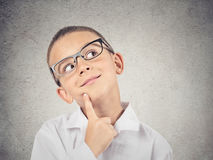 Boy thinking, daydreaming. Closeup portrait, headshot thinking, daydreaming child, boy with glasses, finger on face, looking up, isolated grey wall background royalty free stock image