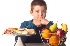 Boy thinking of a food choice. Between fruit or pastries Royalty Free Stock Photo