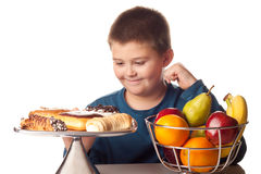 Boy thinking of a food choice. Between fruit or pastries stock image