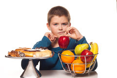 Boy thinking of a food choice. Between fruit or pastries Royalty Free Stock Photography