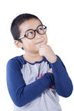 Boy thinking idea and looking at up. Cute schoolboy thinking idea while wearing glasses and looking at up, isolated on white background Royalty Free Stock Image