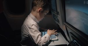 Kid playing pad chess game when traveling by plane at night. Boy thinking over a chess game which he playing on tablet computer during night flight stock video footage