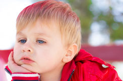 Boy Thinking. Portrait of a little boy with blue eyes leaning and thinking, dazing royalty free stock image