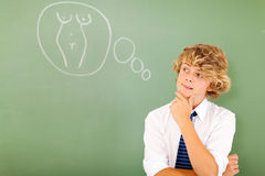 Boy thinking woman. Naughty teenage boy thinking about woman's body in classroom Royalty Free Stock Images