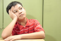 Boy Thinking/Wondering. A photo of a boy with his hand on his cheek and chin as if in deep thought Stock Image