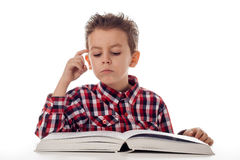 Boy thinking. Young boy in shirt and a big book thinking Stock Photo