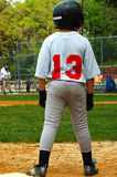 Boy on Third Base. Young boy playing baseball.  He is standing on third  base.  He is wearing a helmut and his shirt says 13.  There is a player and coach Royalty Free Stock Photo