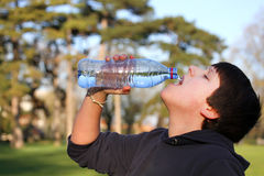 Boy thirsty eagerly drinking water Stock Photography