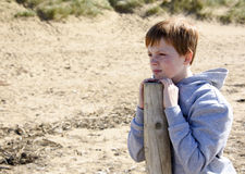 Boy in thought. Young boy, leaning on a post and gazing into the distance at the beach stock photo