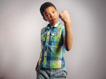 A boy threatening with his fist. A boy threatening with his fist over grey background. Vertical Shot Stock Photo