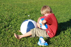 Boy with three balls. Little boy sitting with blue and white balls royalty free stock images