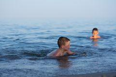 A boy of three years is swimming in the sea at sunset with his brother royalty free stock image