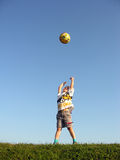 Boy throw ball. In blue sky royalty free stock photography
