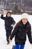 Boy throw snow ball to the running girl.  Royalty Free Stock Photo