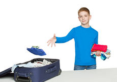 Boy throwing clothes to full luggage bag Royalty Free Stock Image