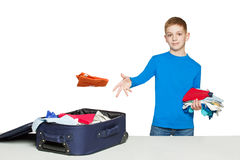 Boy throwing clothes to luggage bag Royalty Free Stock Photo